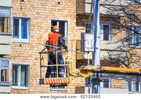 workers in aerial work platform paint light fixture
