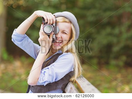 Young Hipster Taking Photo With Retro Photo Camera Sitting On Be