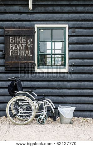 Wheelchair Standing Front Of A House - Bike And Boat Renting