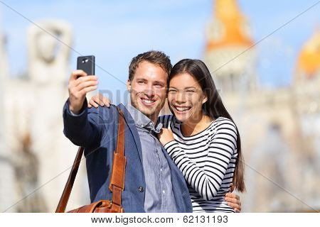 Lovers - young couple happy taking selfie photo with smart phone camera. Modern urban city man and woman having fun taking self portrait picture with smartphone, Catalonia Square, Barcelona, Spain
