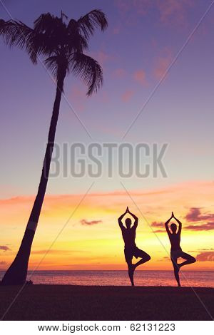 Serene yoga people training in sunset in tree pose meditating outdoors by beach ocean sea. Couple, man and woman working out training in serene ocean landscape. Silhouette against sunset