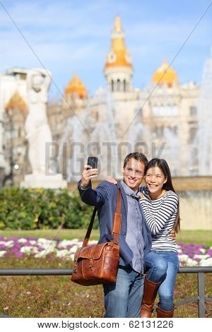 Tourist travel couple taking selfie in Barcelona with smart phone camera. Trendy cool urban city couple, Cauasian man, Asian woman traveling together, Placa de Catalunya, Catalonia Square, Barcelona