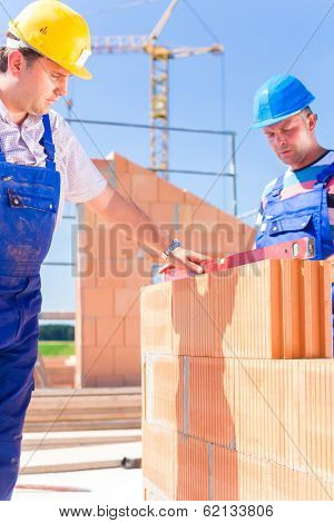 construction site worker or bricklayer with helmets controlling walls with a bubble level or building or laying or bricklaying wall on building