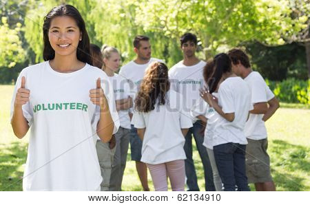 Portrait of confident volunteer gesturing thumbs up at park with friends in backgorund
