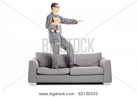 Man in pajamas sleepwalking on sofa isolated on white background
