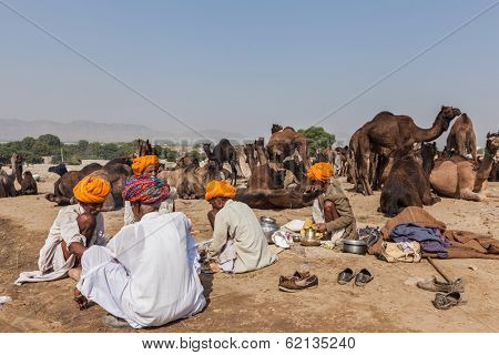 PUSHKAR, INDIA - NOVEMBER 20, 2012: Indian men and camels at Pushkar camel fair (Pushkar Mela) -  annual five-day camel and livestock fair, one of the world largest camel fairs and tourist attraction