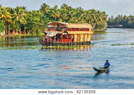KERALA, INDIA - MAY 5, 2010: Tourist houseboat and local man in small boat in backwaters. Kerala backwaters are both major tourist attraction and integral part of local people life in Kerala