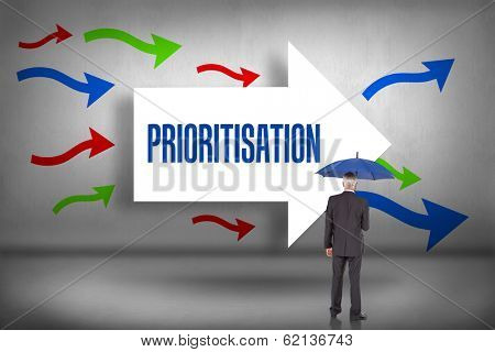 The word prioritisation and businessman holding umbrella against arrows pointing