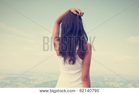 Rear view of standing long hair woman against sky and landscape