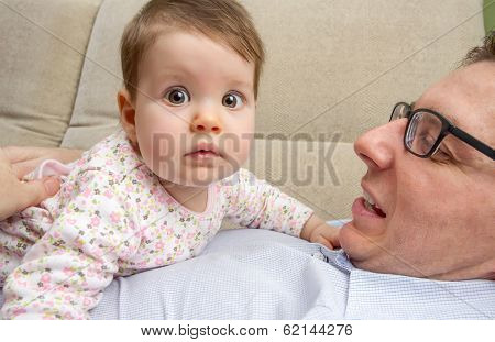Cute baby playing with her happy father