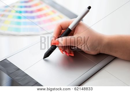 Graphic Designer Working On A Digital Tablet And With Pantone Palette