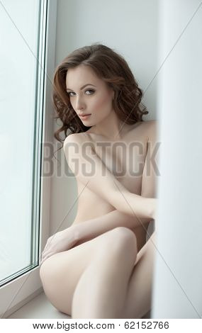 Curvy nude model invitingly looking at camera