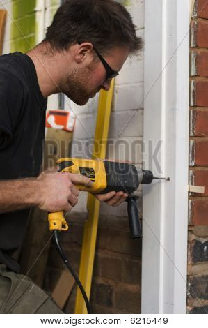Carpenter Using Electric Portable Power Drill To Fit Door Frames