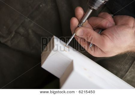 Carpenter Using Powertool To Fix Screws In Doorframe