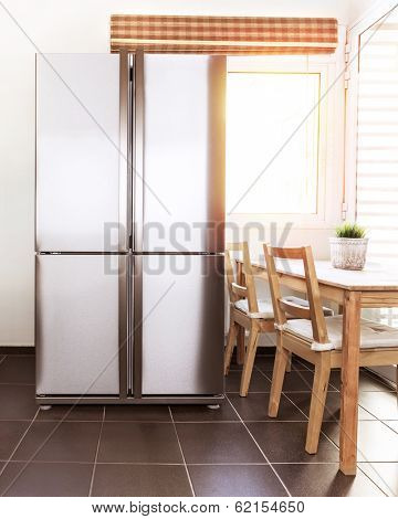 Luxury steel refrigerator on the kitchen, bright sun light from the windows, beautiful apartment interior, stylish fridge, wealth concept