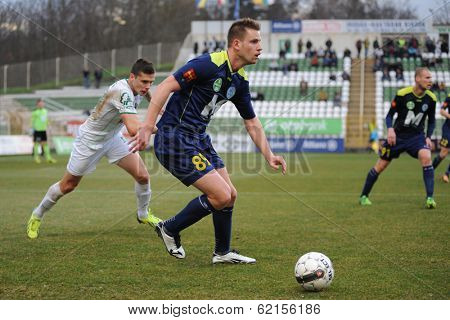 KAPOSVAR, HUNGARY - MARCH 16: Adrian Szekeres (blue 89) in action at a Hungarian Championship soccer game - Kaposvar (white) vs Puskas Akademia (blue) on March 16, 2014 in Kaposvar, Hungary.