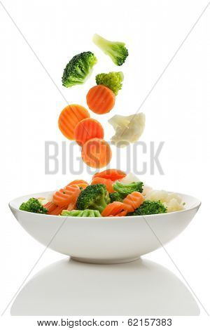 Mixed vegetables falling into a bowl of salad