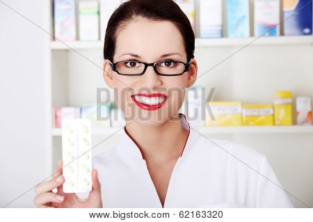 Beautiful woman druggist is holding some tablets.Health care concept.