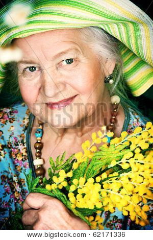 Portrait of a beautiful elderly woman with mimosa flowers. Happy old age.