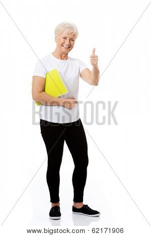 An old woman holding workbook and showing OK. Isolated on white.