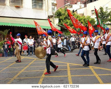 Young Men Carry Flags And Beat Gongs