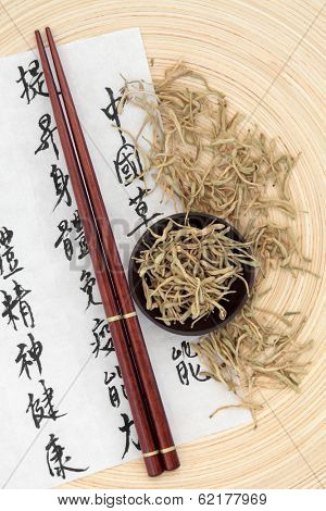 Chinese herbal medicine of dried honeysuckle flowers with mandarin calligraphy script on rice paper describing the medicinal functions to maintain body and spirit health and balance body energy.