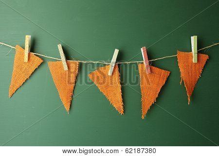Orange Burlap Pennants Hanging on a Green Chalkboard