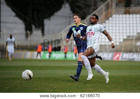KAPOSVAR, HUNGARY - MARCH 16: Mulemo Landry (in white) in action at a Hungarian Championship soccer game - Kaposvar (white) vs Puskas Akademia (blue) on March 16, 2014 in Kaposvar, Hungary.