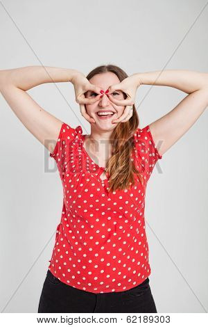 Smiling Attractive Woman Through Finger Goggles