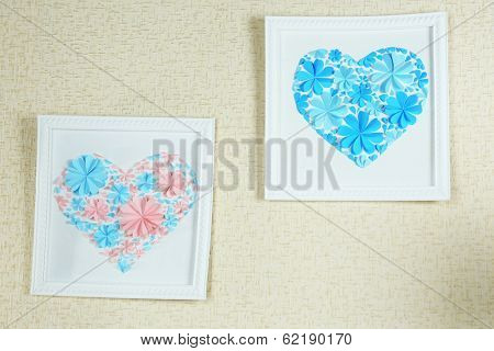 Beautiful handmade picture with heart from paper flowers on wall