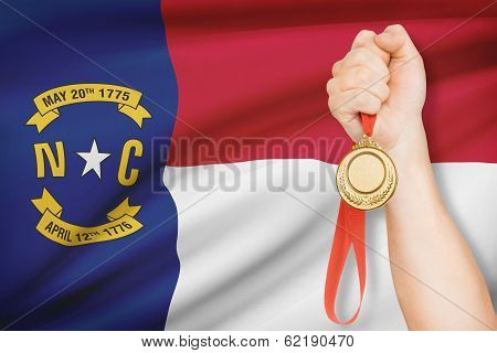 Medal In Hand With Flag On Background - State Of North Carolina. Part Of A Series.