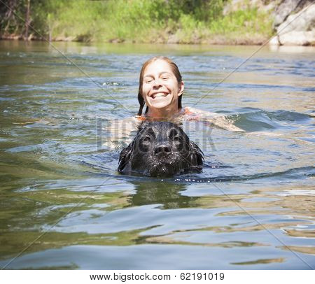 a girl and a big lab dog swimming in the water