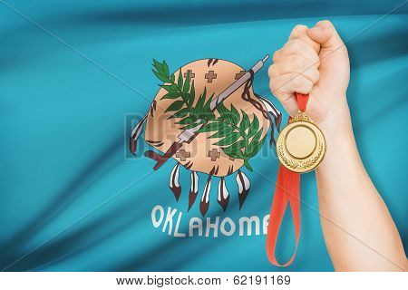Medal In Hand With Flag On Background - State Of Oklahoma. Part Of A Series.
