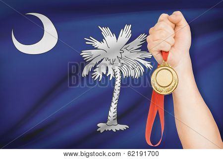 Medal In Hand With Flag On Background - State Of South Carolina. Part Of A Series.