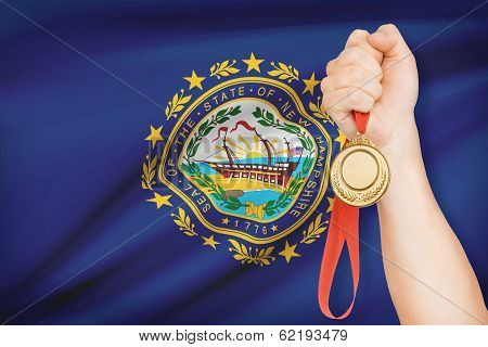 Medal In Hand With Flag On Background - State Of New Hampshire. Part Of A Series.