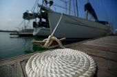 stock photo of coiled  - Coil of the rope on the wooden pier tied up to the yacht - JPG