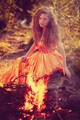 stock photo of witchcraft  - Beautiful witch in the woods near the fire - JPG