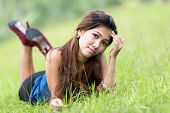 foto of filipina  - Beautiful young Filipina woman enjoying nature lying on her stomach facing the camera in a green grassy field with a thoughtful expression - JPG
