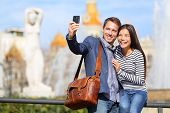 Happy urban city couple on travel in Barcelona taking selfie self portrait photograph with smart pho