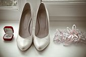 picture of garter  - pair of gold wedding rings in a red box cream bridal shoes lace garter
