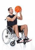 stock photo of paralympics  - Man in wheelchair playing basketball - JPG