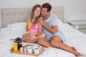 pic of bed breakfast  - Happy young couple having breakfast in bed at home - JPG
