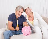 stock photo of raid  - Senior couple raiding a piggybank sitting with a hammer in the mans hand and looks of anticipation and glee - JPG