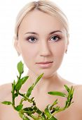 The beautiful young woman with a green bamboo isolated