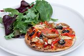 Home Baked Vegan Mini Pizza With Ruccola Salad On Plate