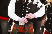 stock photo of bagpiper  - Color shot of a person holding a traditional bagpipe - JPG