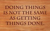 Doing things is not the same as getting things done - on wooden red oak background