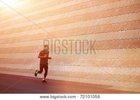 At sunset light muscular build sportsman running with speed
