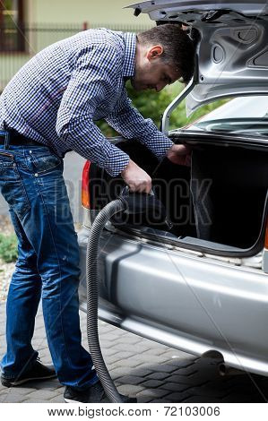 Man Hoovering Trunk Before A Trip