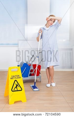 Tired Female Maid Holding Mop